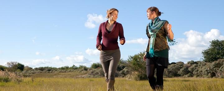 Vrouwen passen gesprekstherapie toe bij een wandeling in de buitenlucht voor de cursus Narratieve therapie