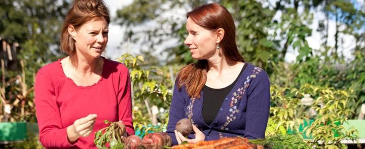 Vrouwen in gesprek in moestuin over natuurvoeding bij de cursus Natuurvoedingsadviseur