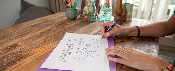 Vrouw maakt schriftelijke oefening bij cursus Numerologie
