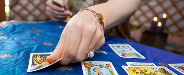Kaartlezer legt tarotkaarten op tafel bij cursus Tarot
