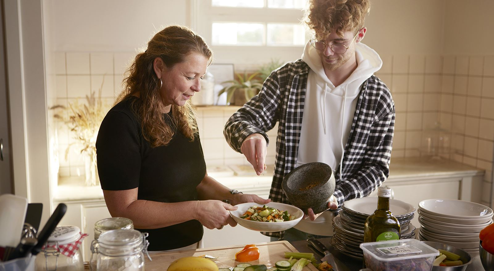 Voedingsdeskundige en cliënt bereiden plantaardig eten bij de opleiding Plantaardige voeding
